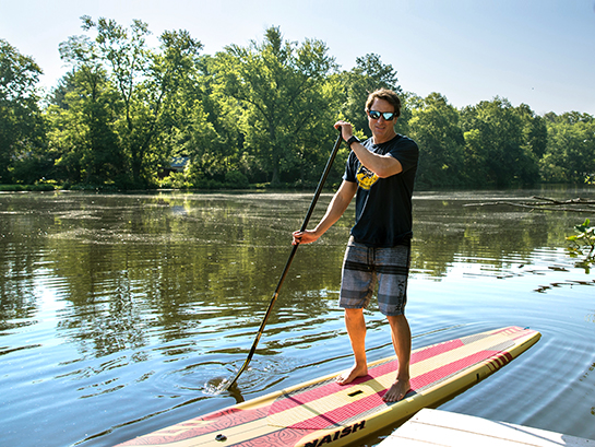 Will Sodano paddle boards across Peddie Lake